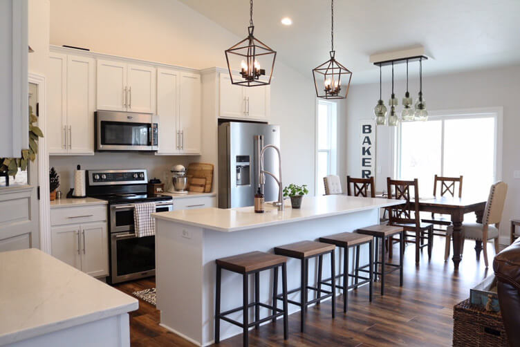 Two industrial style pendants hang over the island of a white kitchen.